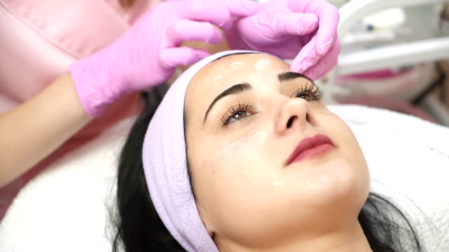 beautiful young girl getting a facial cleansing procedure. - facial stock videos & royalty-free footage