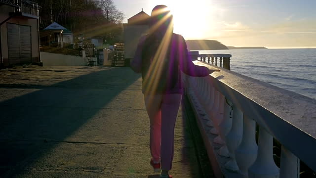 Beautiful young girl goes to sea with stone parapet. Pink clothes, spring time, Slow motion. Full shot video