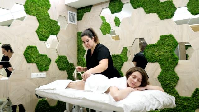 schöne junge mädchen mit massage in spa-salon - menschlicher rücken stock-videos und b-roll-filmmaterial