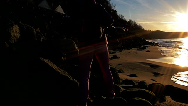 Beautiful young girl in background of sun's rays is walking along rocks on sea coastline. Pink clothes, spring time, Slow motion. Medium shot video