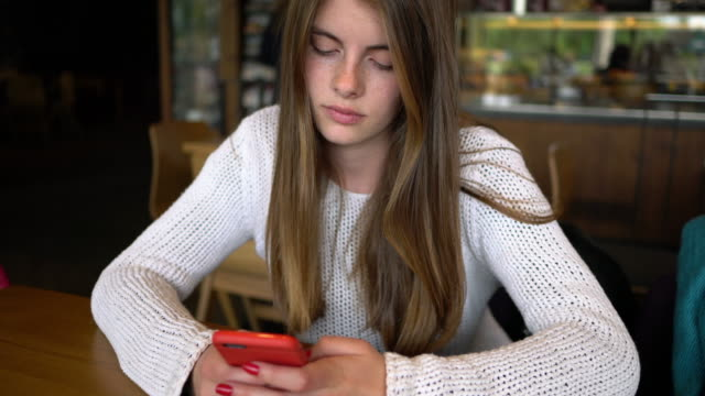 beautiful young girl in cafe texting - furioso video stock e b–roll
