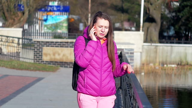 Beautiful young girl in park by lake, talking on phone, go to camera. Pink clothes, springtime, Slow motion. Medium shot video