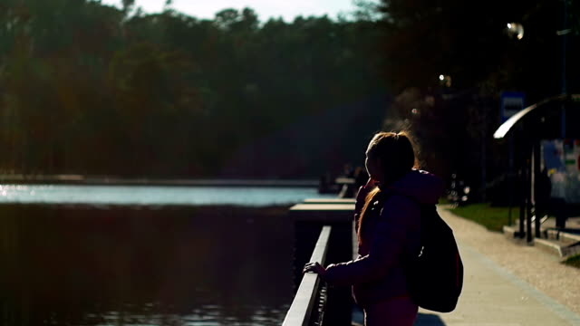 Beautiful young girl in park looking lake, talking phone, evening. Pink clothes, springtime, Slow motion video