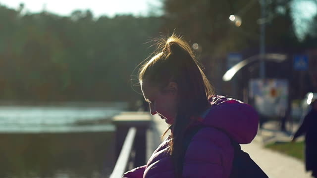 Beautiful young girl in park, on lake shore make selfie. Pink clothes, springtime, Slow motion, Close Up Shot video
