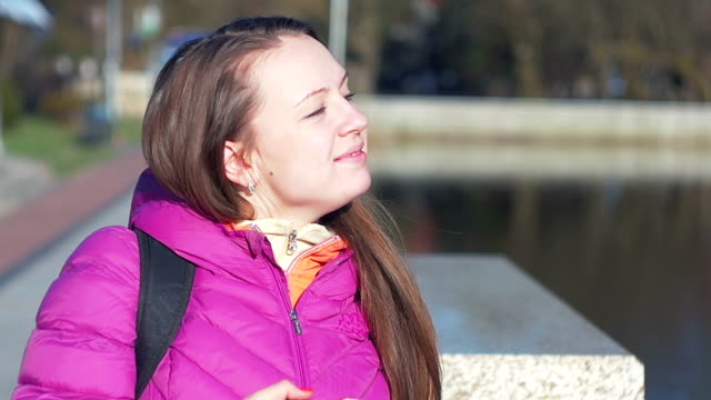 Beautiful young girl in park, on lake, smiling and enjoying sun. Pink clothes, springtime, Slow motion. Close up shot video