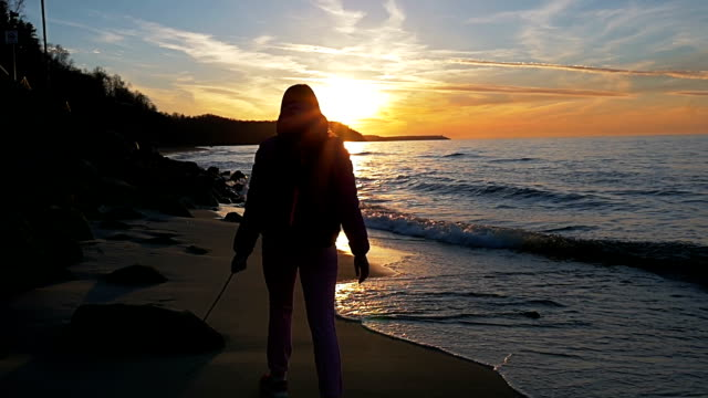 Beautiful young girl is walking along the beach in the background of sun rays. Pink clothes, spring time, Slow motion. Medium Shot video