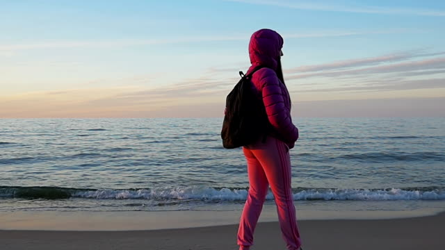 Beautiful young girl looks at calm sea and blue sky. Turned on camera. Relaxation. Pink clothes, spring time, Slow motion. Medium Shot video
