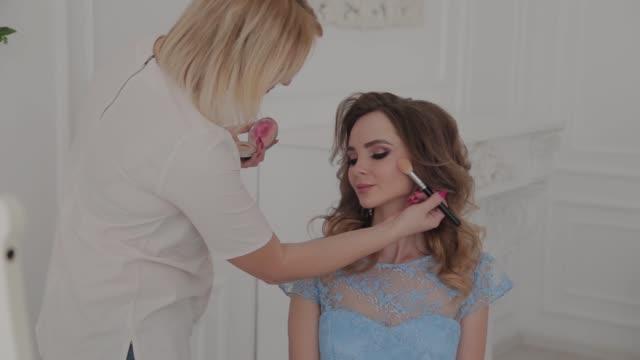 Beautiful young girl makes makeup artist
