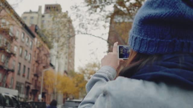 vidéos et rushes de belle jeune fille rend la photo sur le téléphone - photophone
