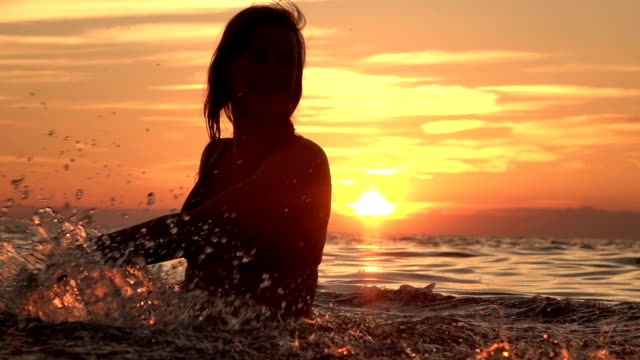 slow motion: beautiful young girl playing with water in ocean at golden sunset - pesche bambino video stock e b–roll