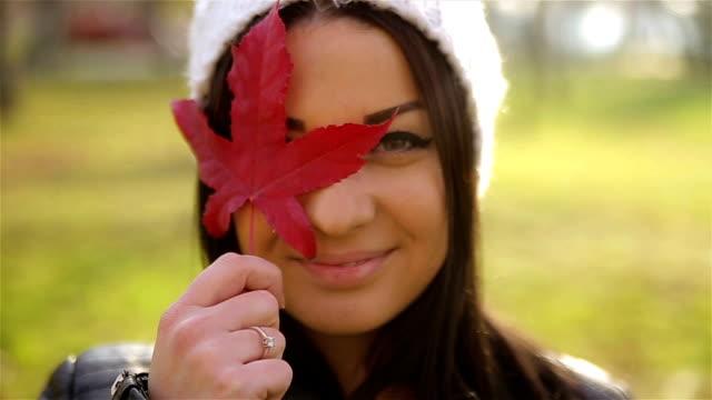 Retrato de joven hermosa con hojas rojas en otoño - vídeo