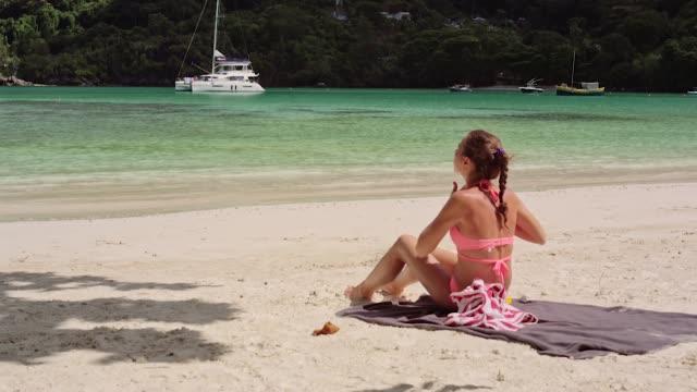 en vacker ung flicka sitter på stranden och utstryk hennes kropp med solskydd. - indiska oceanen bildbanksvideor och videomaterial från bakom kulisserna