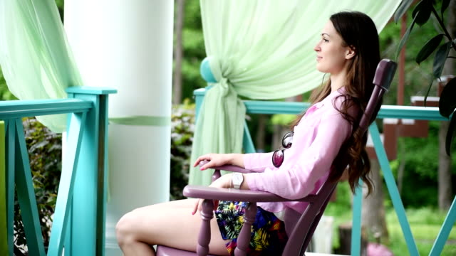 beautiful young girl sitting in a chair on the veranda happy beautiful girl enjoying relaxation while sitting in a wooden rocking chair. girl sitting on the outdoor veranda Country restaurant. clear sunny summer day. girl wearing a pink shirt and short shorts. one person. she sits sideways to the camera. in the background porch railing and wood rocking chair stock videos & royalty-free footage