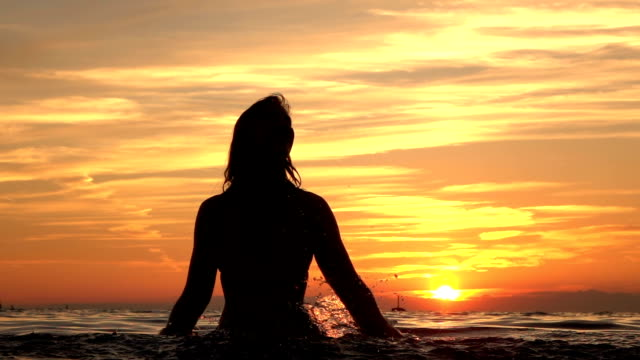 slow motion: beautiful young girl sprinkling water in ocean at golden sunset - pesche bambino video stock e b–roll