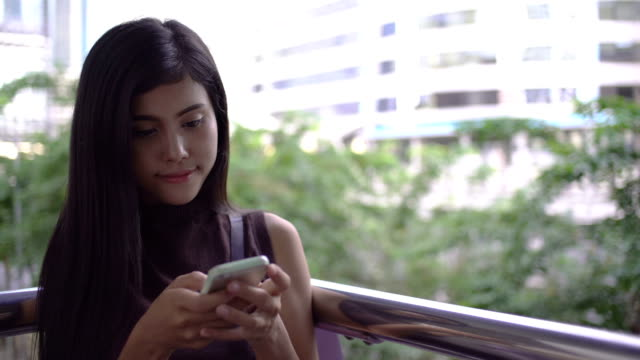 Beautiful young girl uses a smartphone on a city background. video