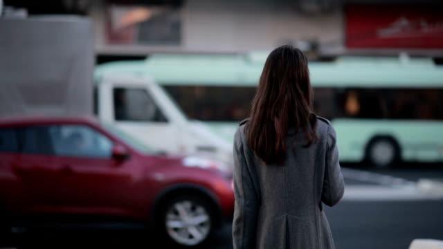 美しい若い少女ウェイティングで横断歩道 - 交通信号機点の映像素材/bロール