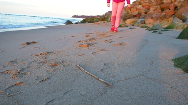 Beautiful young girl walking along beach. Pink clothes, spring time, Slow motion. Close up of feet video
