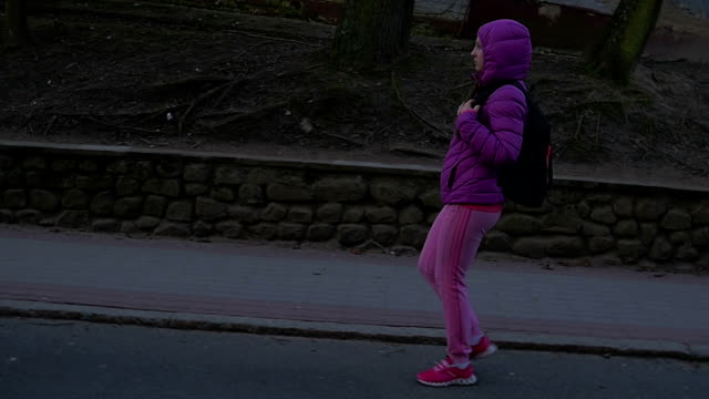 Beautiful young girl walking in shade of tree, walking down hill. Pink clothes, spring time, Slow motion. Full shot video