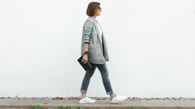 Beautiful young girl walking past white wall and posing with handbag.