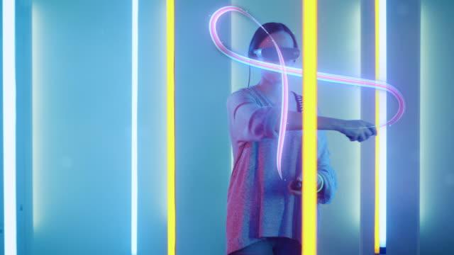 schönes junges mädchen tragen virtual-reality-kopfhörer zieht abstrakte linien und figuren mit joysticks / controller. kreative junge mädchen macht konzeptkunst mit augmented reality. retro-neonröhren umringen sie. computergrafik. - künstlerischer beruf stock-videos und b-roll-filmmaterial