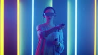 istock Beautiful Young Girl Wearing Virtual Reality Headset Draws Abstract Lines and Figures with Joysticks / Controllers. Creative Young Girl Does Concept Art with Augmented Reality. Playing Online Video Game. Neon Retro Lights Surround Her. 1002136840