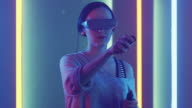 istock Beautiful Young Girl Wearing Virtual Reality Headset Draws Abstract Lines and Figures with Joysticks / Controllers. Creative Young Girl Does Concept Art with Augmented Reality. Playing Online Video Game. Neon Retro Lights Surround Her. 1002137190