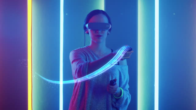 Beautiful Young Girl Wearing Virtual Reality Headset Draws Abstract Lines and Figures with Joysticks / Controllers. Creative Young Girl Does Concept Art with Augmented Reality. Playing Video Games. Neon Retro Lights Surround Her. Computer Graphics.