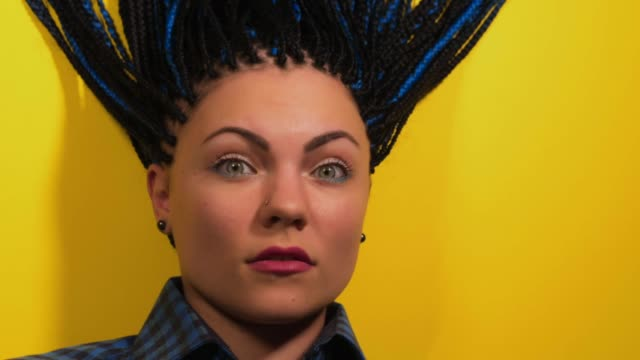 Beautiful young girl with african blue braids is surprised and looks at the camera. Stop motion animation. Woman on bright yellow background. Dyed Hair moves. Hipster video