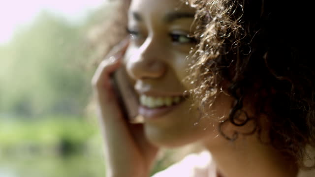 Beautiful young girl with dark curly hair using her cell phone, outdoor. video