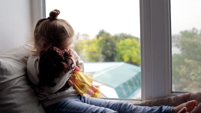 beautiful young girl with doll sitting on a window sill - femminilità video stock e b–roll