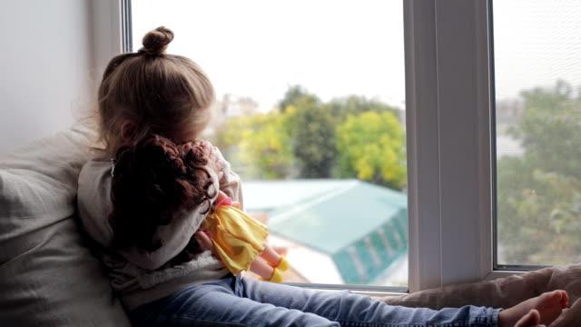 stockvideo's en b-roll-footage met mooi jong meisje met pop zittend op een vensterbank - vrouwelijkheid