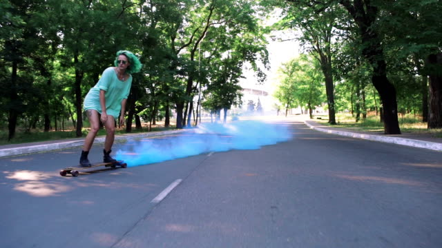 Beautiful young girl with green hair riding on longboard with blue smoke in park, slow motion, tracking shot video