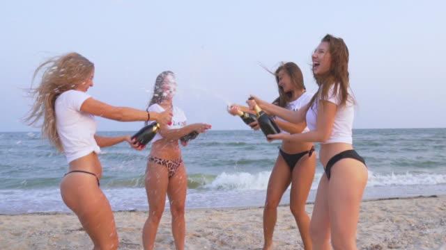 Mooie jonge meisjes vieren aan de kust. Kip-partij. Schudden van een bizarre fles Champagne en laten spuiten video