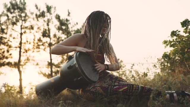 beautiful young hippie woman with dreadlocks playing on djembe. funky woman drumming in nature on an ethnic drum at sunset or sunrise - hippy video stock e b–roll