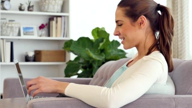 Beautiful young Hispanic woman laughs while using laptop video