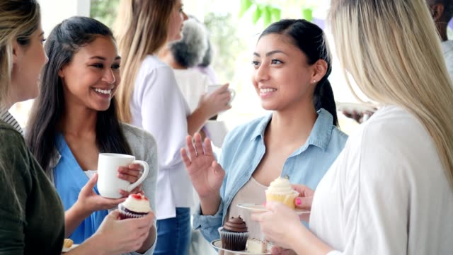 Beautiful young Hispanic woman talks with group of friends during charity bake sale Cheerful young Hispanic woman gestures as she talks with female friends at a charity bake sale. The women smile and laugh with one another while enjoying coffee and cupcakes. party social event stock videos & royalty-free footage