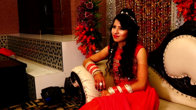 Beautiful young Indian Bride sitting on Luxury sofa in wedding reception hall