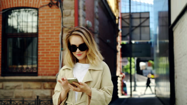 beautiful young lady is holding smartphone and using it walking along street in modern city. technology, beautiful happy people and youth lifestyle concept. - capelli biondi video stock e b–roll