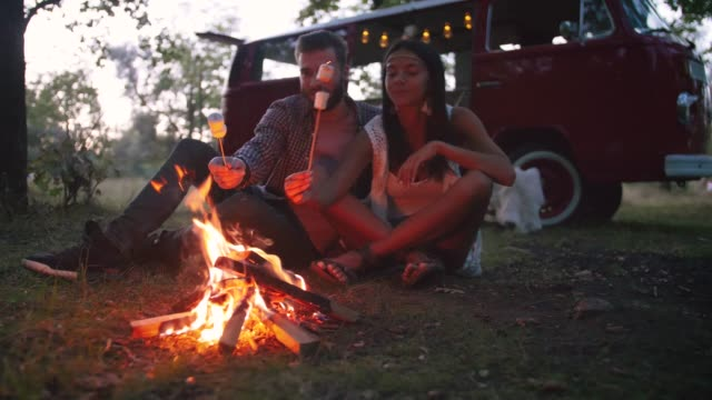 beautiful young mixed race couple roasting marshmallows over a campfire while enjoying their road travel, slow motion, dolly - date night stock videos & royalty-free footage