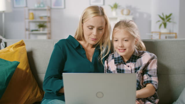 Beautiful Young Mom and Her Cute Little Daugther Use Laptop while Sitting on a Sofa at Home. Family Spending Time Together Watching Videos and Cartoons on Computer.