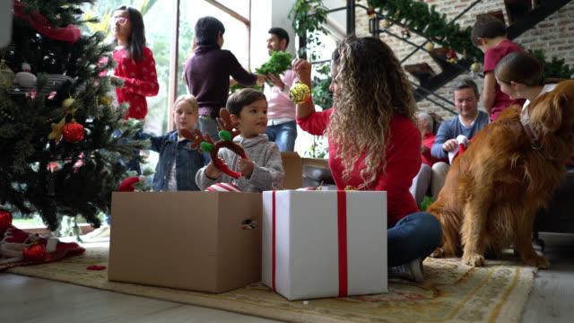 stockvideo's en b-roll-footage met mooie jonge moeder en zoon het nemen van kerst ornamenten uit doos terwijl familie is praten en plezier versieren op de achtergrond - christmas family
