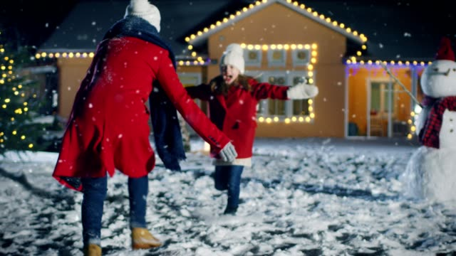 vídeos de stock e filmes b-roll de beautiful young mother returns home, her cute little daughter meets her with the open arms, they embrace, and spin - hug. happy winter evening with family reunion.  falling snow and idyllic house decorated for christmas eve. - family christmas