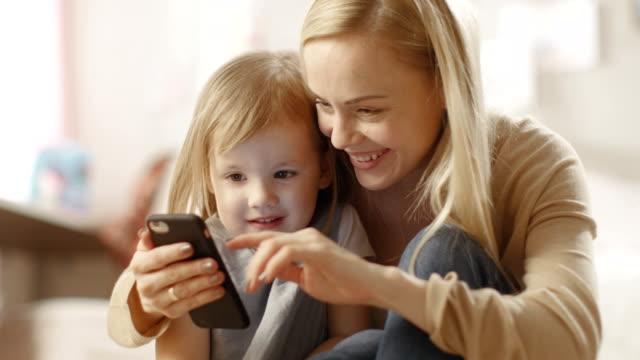 vacker ung mamma sitter med sin lilla dotter och visar henne något intressant på en smartphone. barnens rum är rosa och full av leksaker. - digital reading child bildbanksvideor och videomaterial från bakom kulisserna