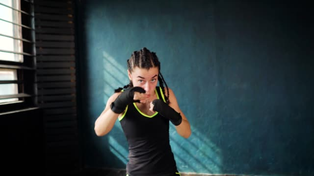 beautiful young moving boxing woman training punching in fitness studio
