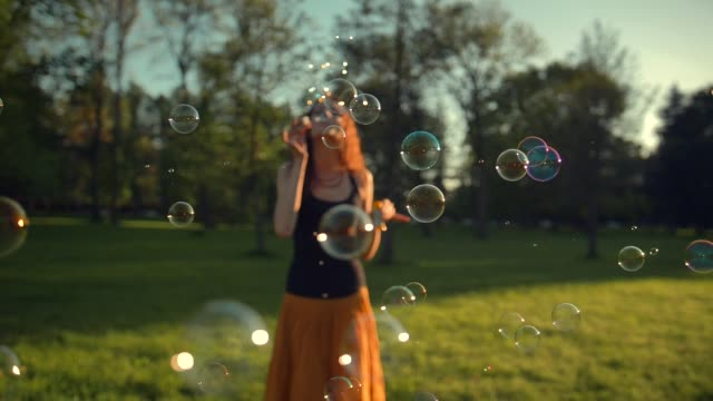 Beautiful young redhair girl blowing soap bubbles outdoors. Sunrise Beautiful young redhair girl blowing soap bubbles outdoors. Slow motion shot of childhood time in adult age. Fun under the rays of the sun. Sunrise. Focus on bubbles. effortless stock videos & royalty-free footage