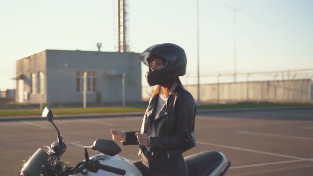vídeos de stock e filmes b-roll de beautiful young red-haired woman motorcyclist dancing on her custom bike in black motorcycle helmet - helmet motorbike