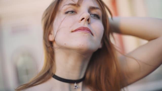 vídeos de stock e filmes b-roll de beautiful young red-haired woman motorcyclist removes helmet on sunset - helmet motorbike