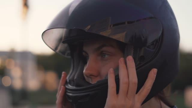 vídeos de stock e filmes b-roll de beautiful young red-haired woman motorcyclist with black motorcycle helmet - helmet motorbike
