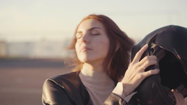 vídeos de stock e filmes b-roll de beautiful young red-haired woman motorcyclist with black motorcycle helmet. girl  biker undresses her helmet - helmet motorbike