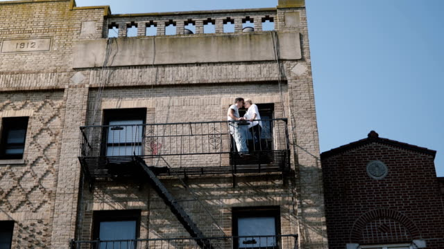 Beautiful young romantic couple standing together at a small balcony of old vintage building, enjoying view of New York